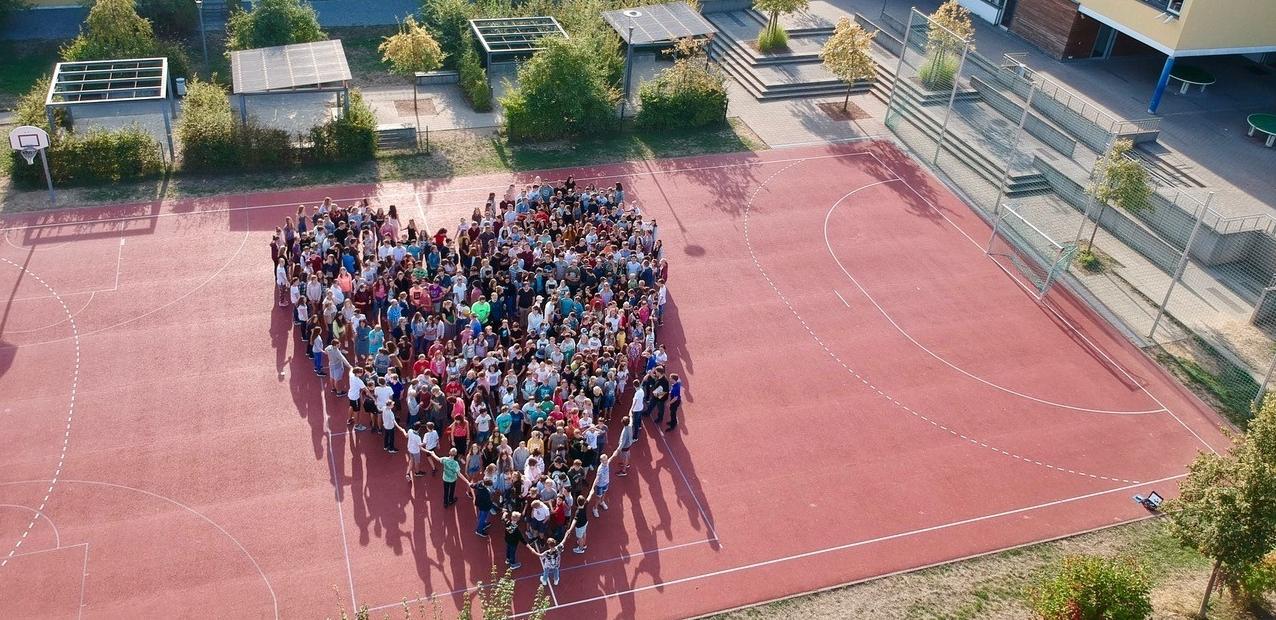 Die Schulgemeinschaft des PDG formt ein Herz auf dem Pausenhof
